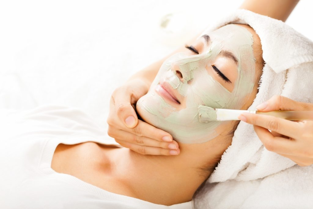 Young beautiful woman with clay facial mask