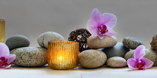 concept of spa, massage, yoga, wellbeing or feng shui with mineral pebbles, fresh orchid flowers and candles, panoramic still life